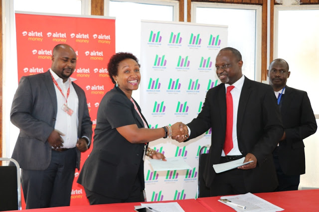 Maendeleo Bank Managing Director Ibrahim Mwangalaba (2nd right) exchanges documents with Airtel Tanzania Communications Director Ms.Beatrice Singano (2nd left) during the launch of a new service that gears at simplifying operations of informal savings and cooperative groups – village community banks (Vicoba) in Dar es salaam..